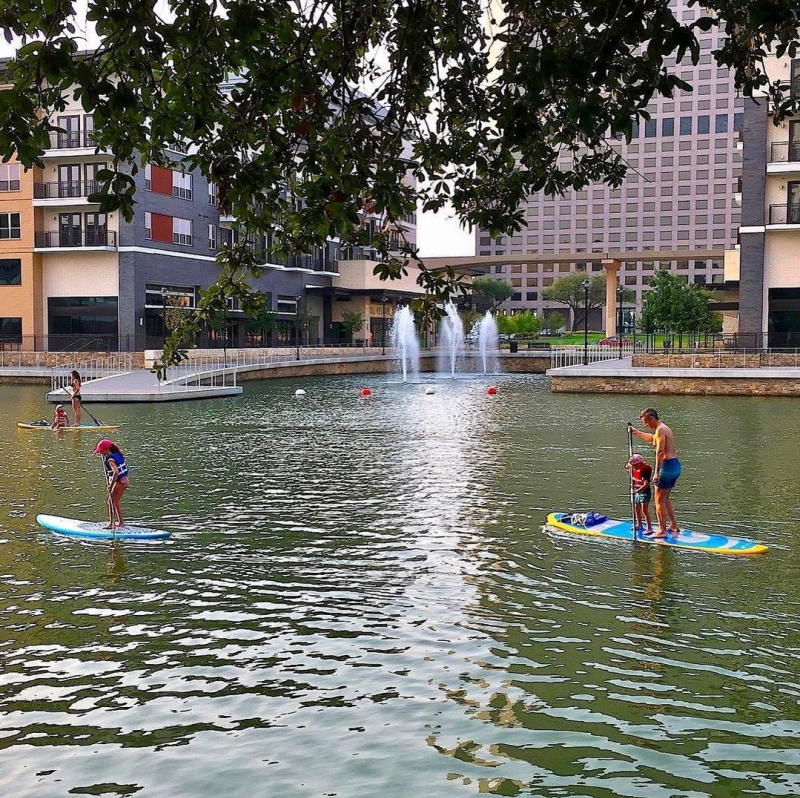 Man And Child Paddle Boarding On Lake Carolyn In Irving, TX