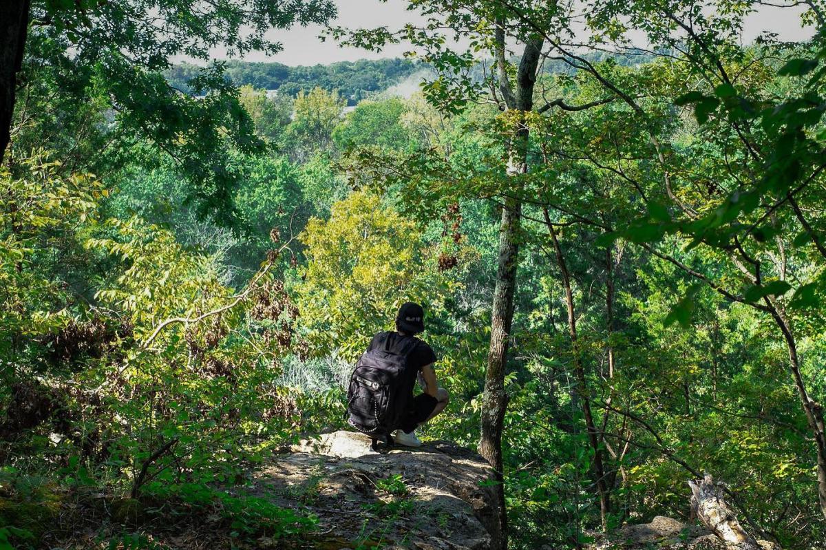 climber atop a bluff overlooking a river