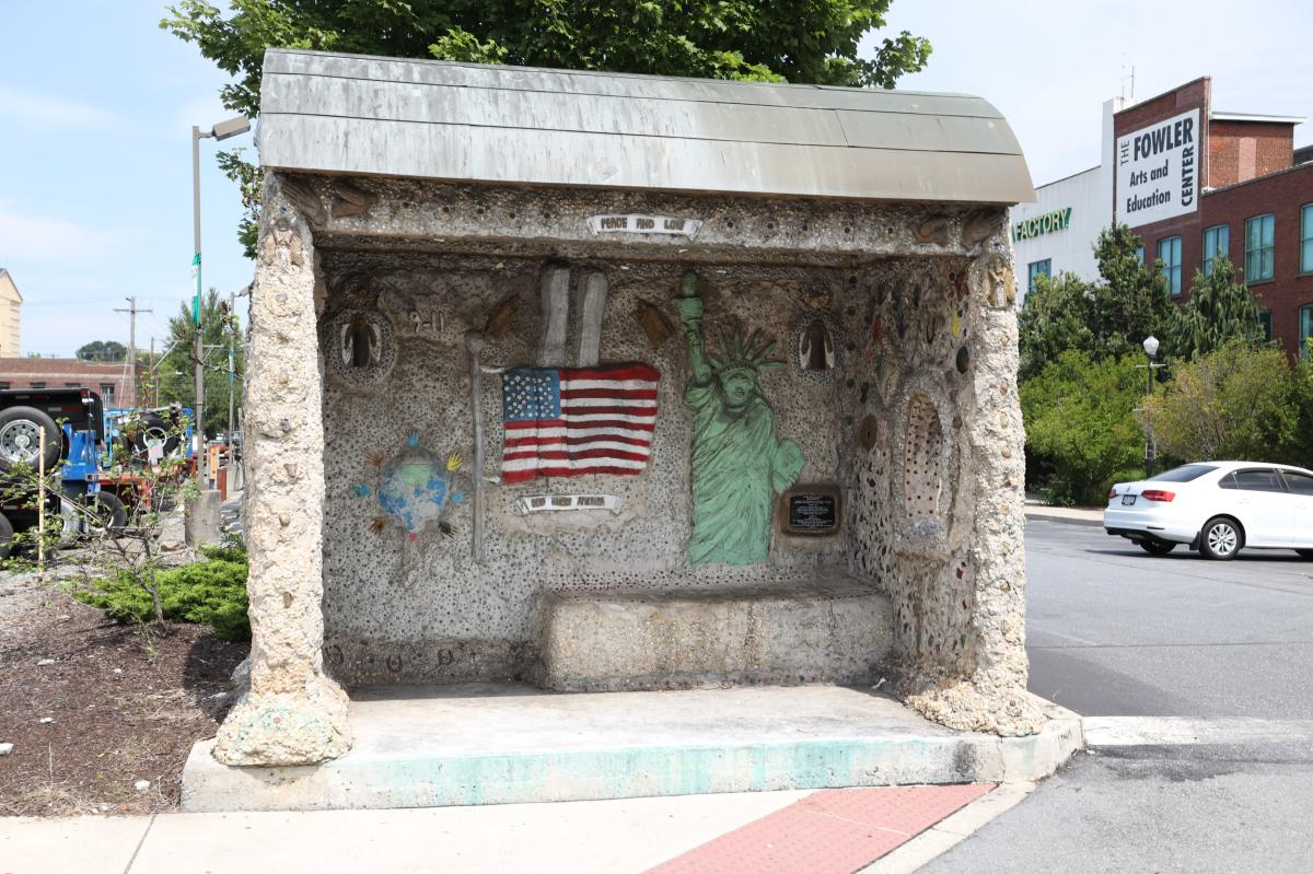 """Mr. Imagination Bus Shelter (Mosaic / Sculpture / Structure), depicting an American Flag, the Statue of Liberty, and a tribute to September 11th featuring the words """"Peace and Love.""""."""