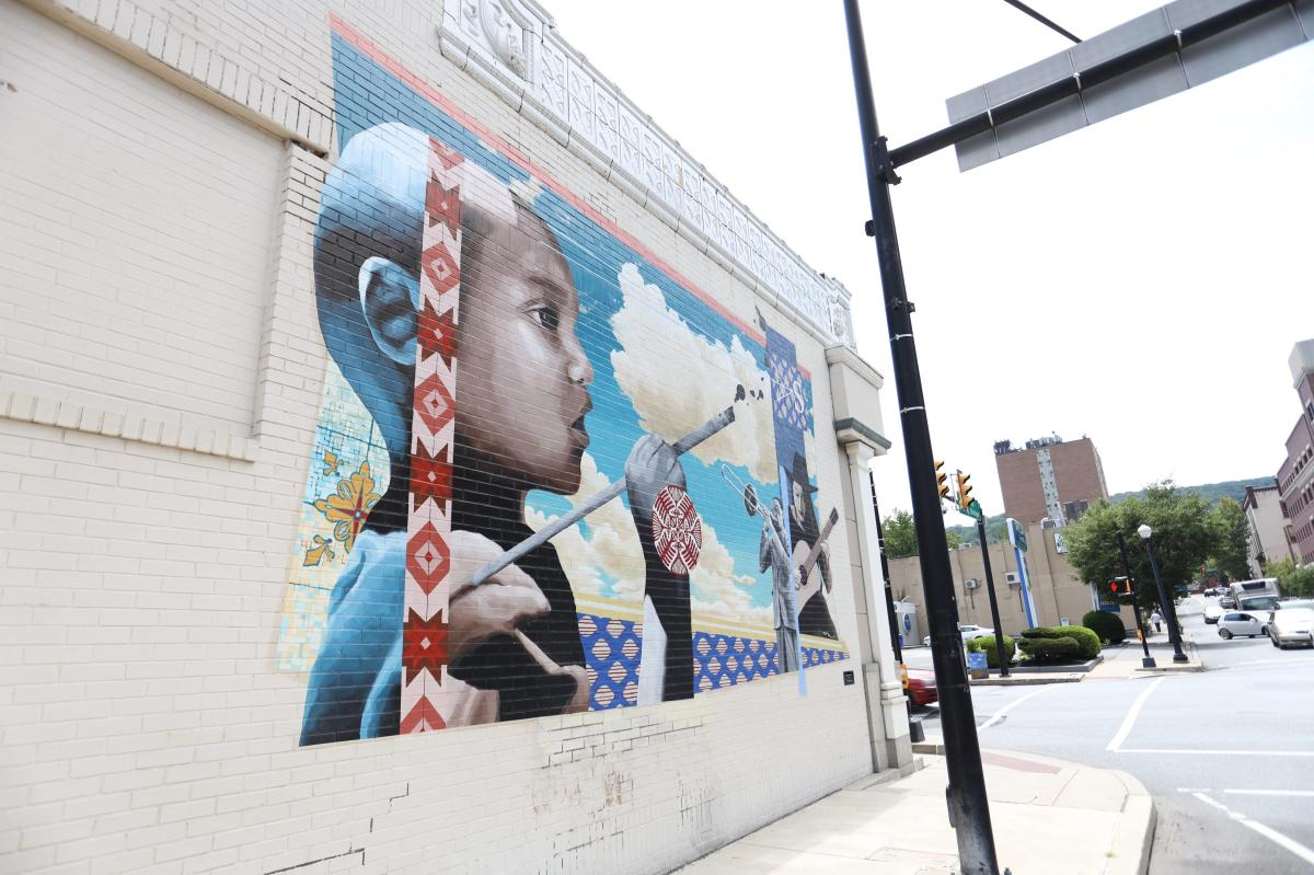 Southbound (Mural) depicting a child painting, a man playing the trombone, and a woman playing guitar.