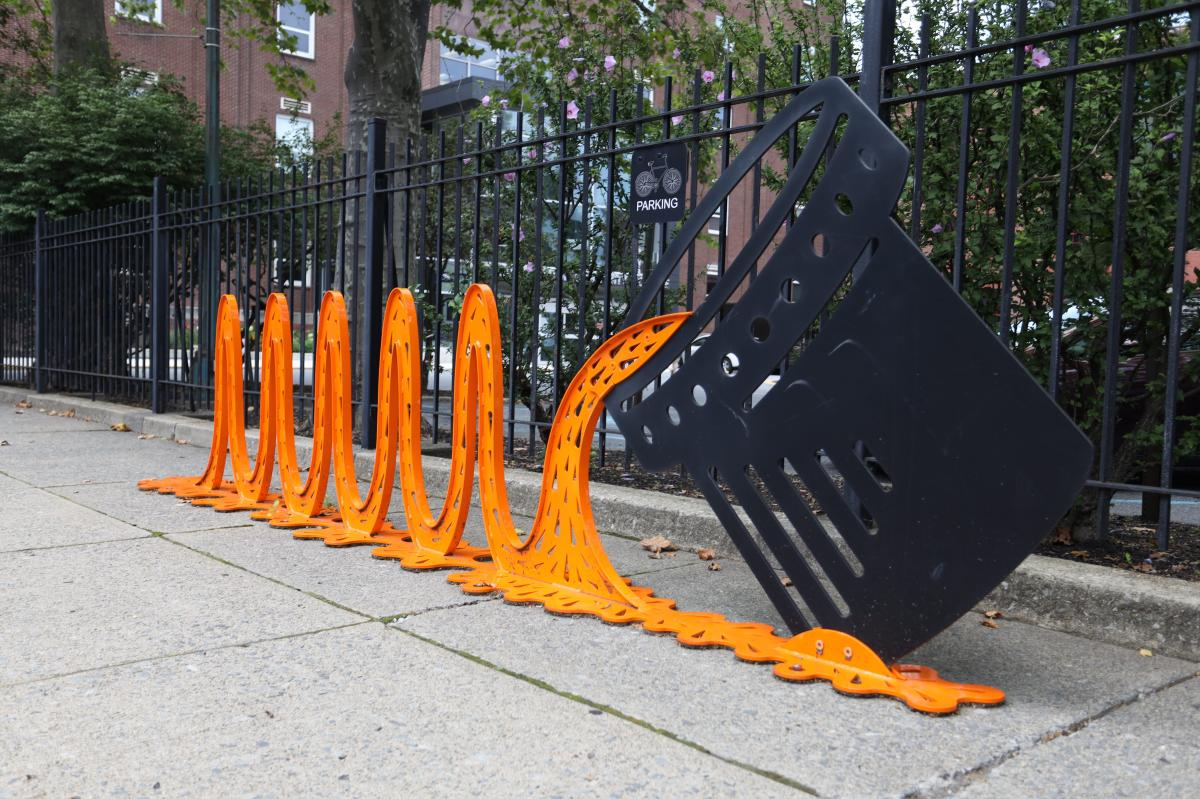Molten Metal (Bike Rack), a large metal bucket pours orange molten steel onto the street, which rises and falls to create slots for bikes to be locked onto.
