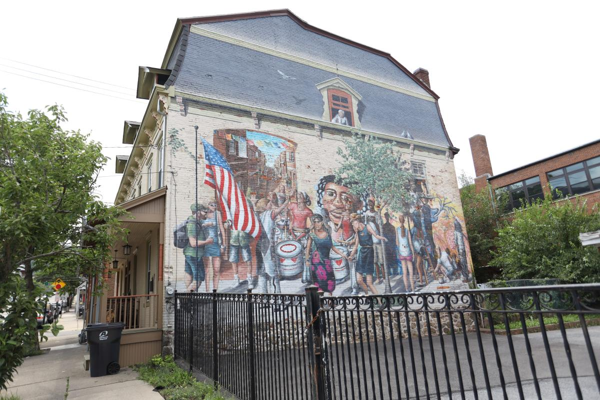 Hayes Street Mural (Mural), Bella Pintura Inc. depicts a diverse group of historical and modern figures celebrating with an American flag, drums, and dancing.