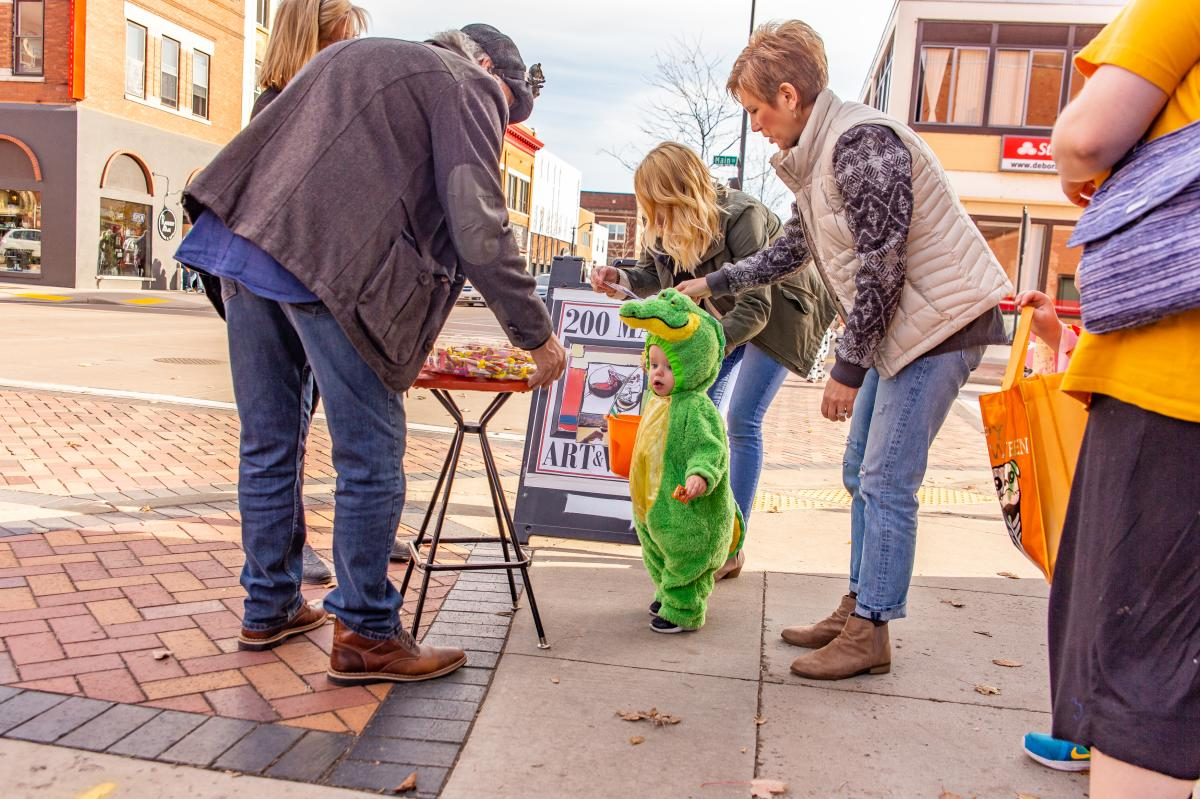 Toddler dressed in a green gator costume trick or treating in Downtown Eau Claire