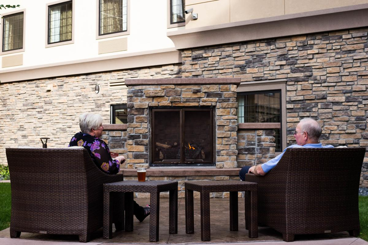 Relaxing in front of outdoor fireplace at Staybridge Suites in Altoona, WI