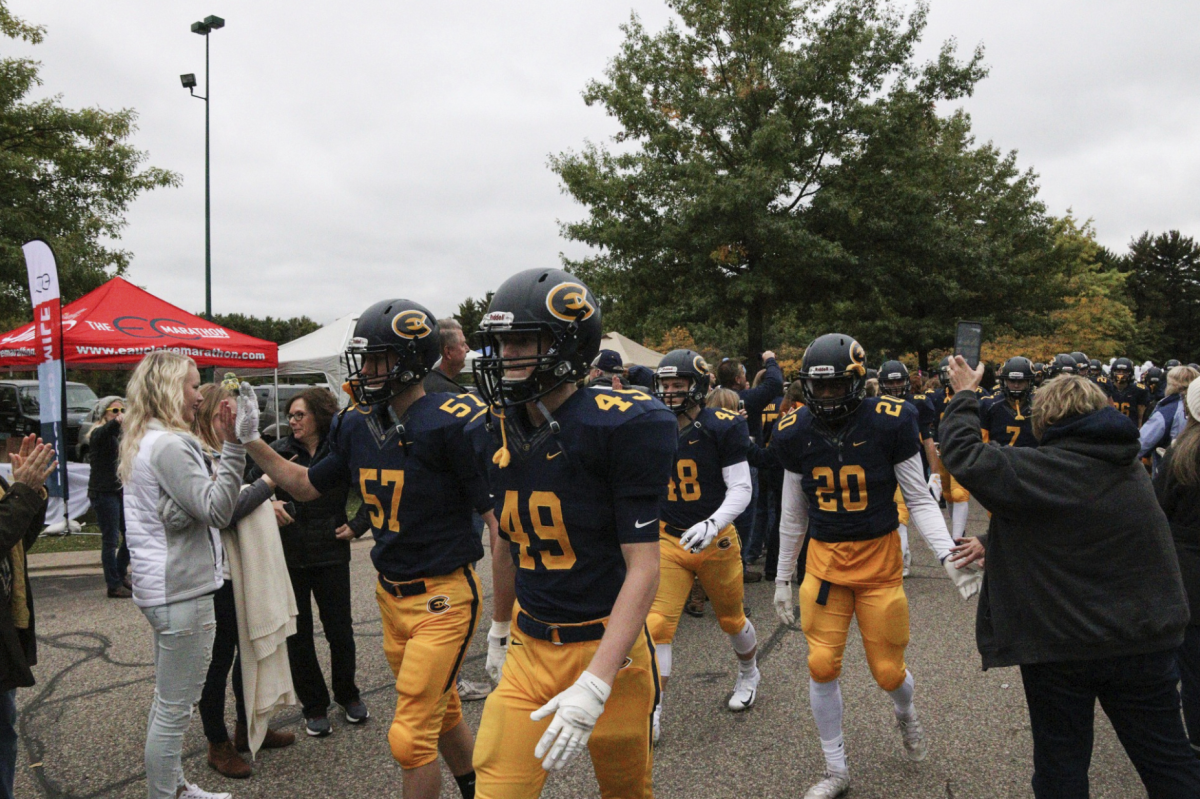 Blugold Football players walking through a crowd homecoming weekend