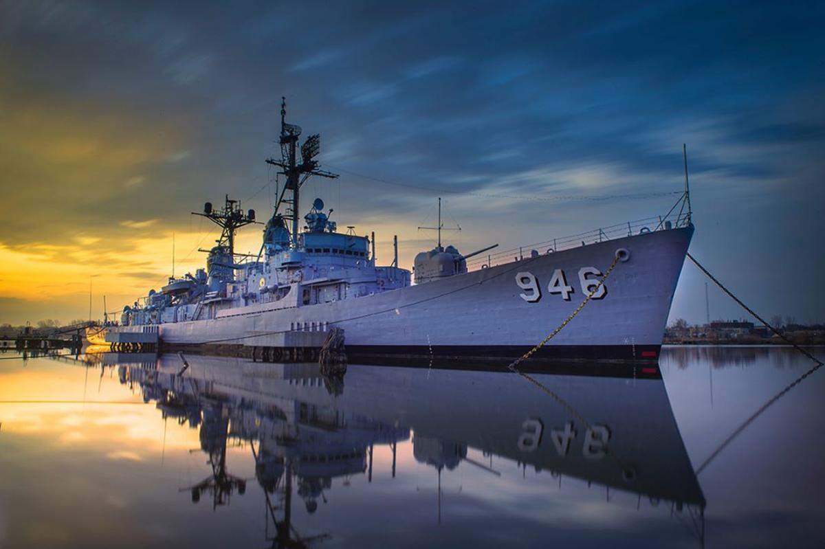 USS Edson reflecting off the water in Bay City with a blue-orange sky behind