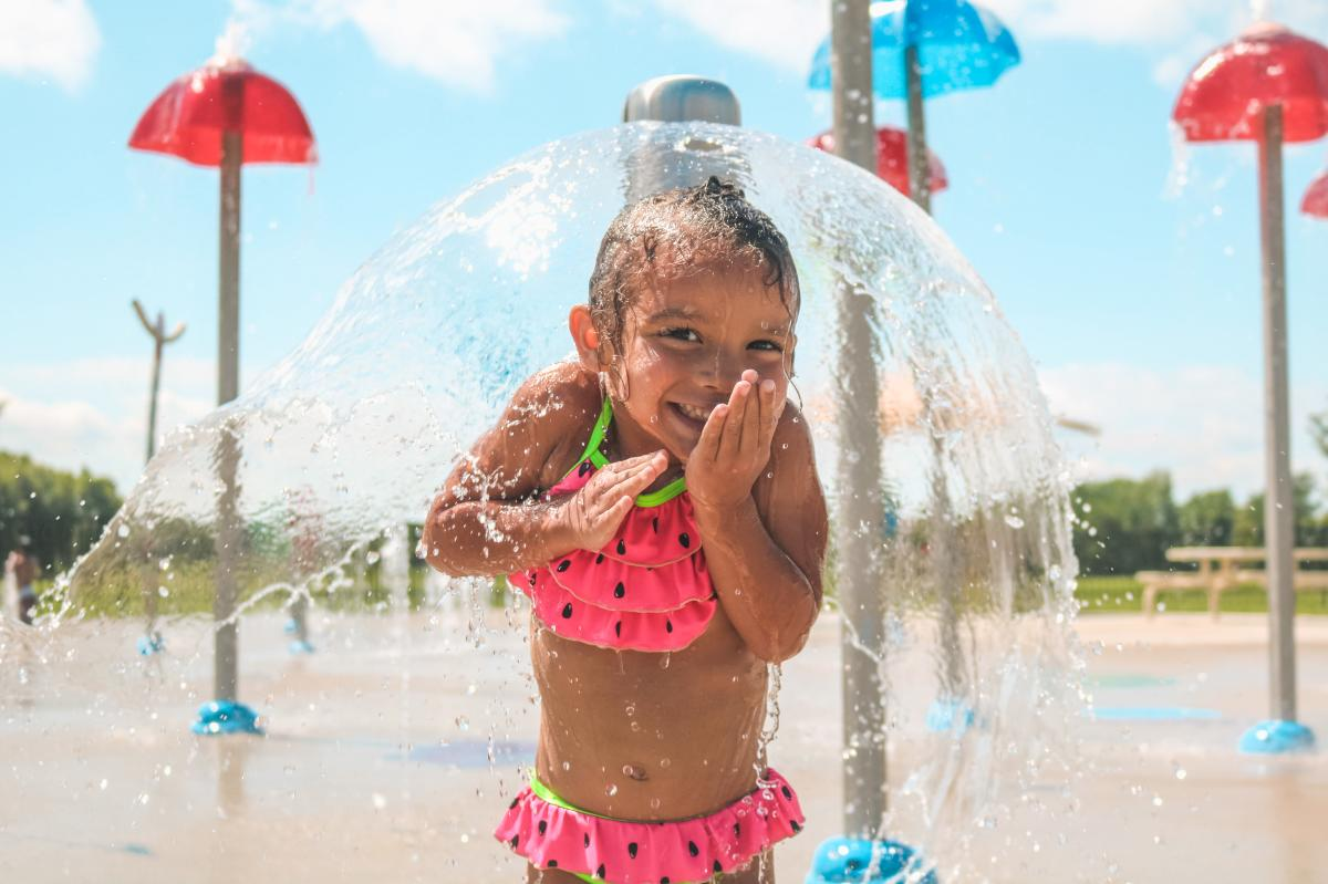 A child poses at the splash pad