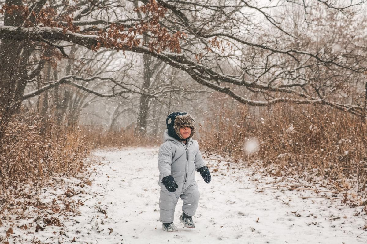 A toddler hikes in a snowsuit