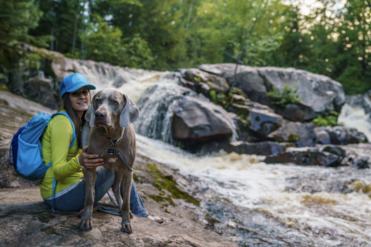 A woman and her dog in front of Yellow Dog Falls in Big Bay