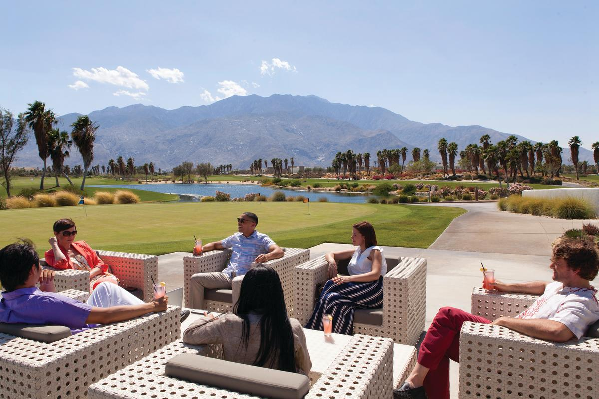 People meeting on a golf course with mountains in the background.
