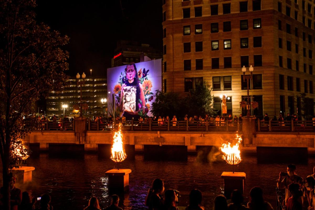 Braziers burn on the river and a mural of a young girl is illuminated in the background.