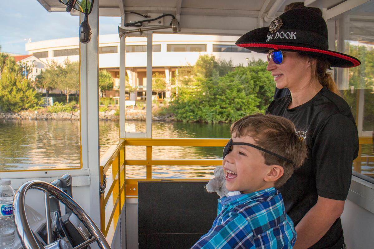 A kid wearing an eye patch and helping steer the Pirate Water Taxi boat.