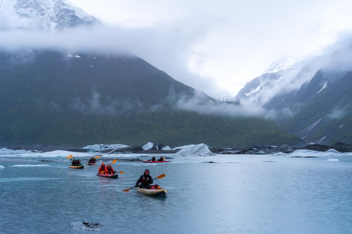 kayakers paddling in a glacial lake
