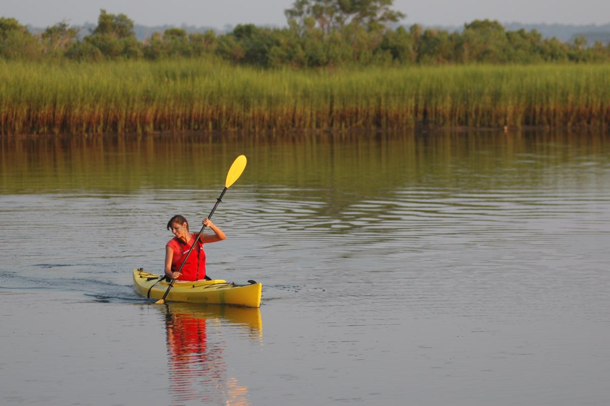 Woman in kayak in salt marsh