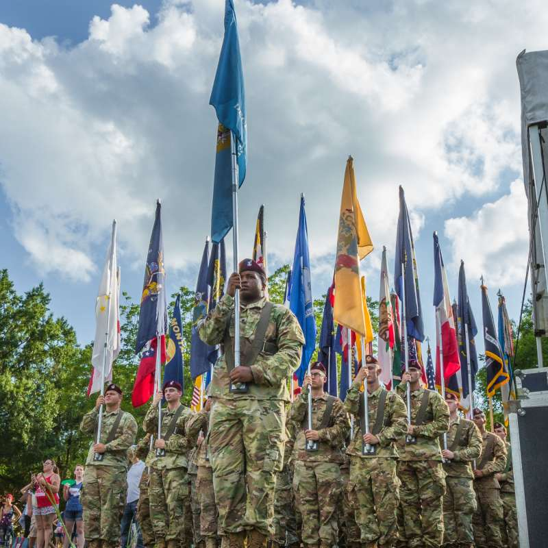 Several Army soldiers holding a variety of flags in formation