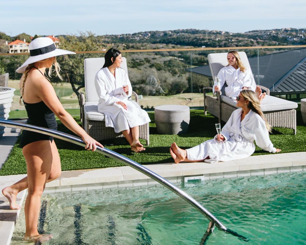 four women lounge at Omni Barton Creek Resorts pool in Austin Texas