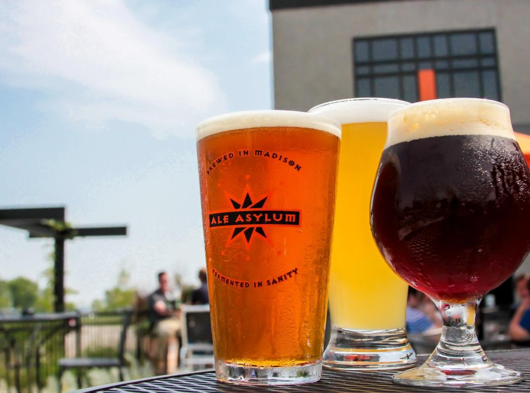 Beers from Ale Asylum sit on an outdoor patio table