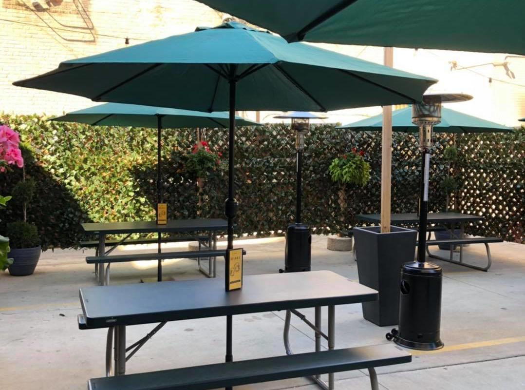 A picnic table with umbrella on the patio of Dotty Dumpling's Dowry.