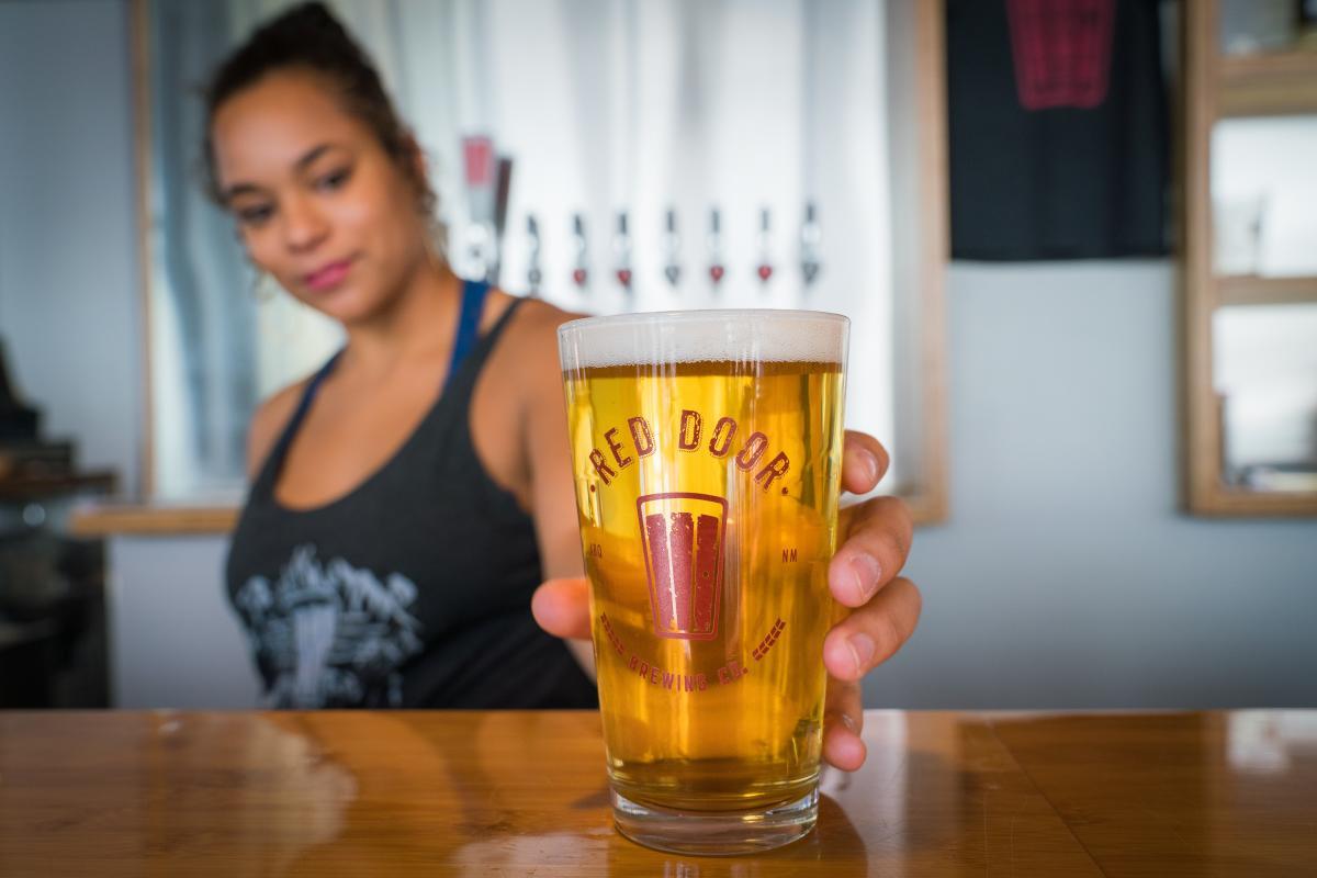 Bar tender serving beer at Red Door Brewery