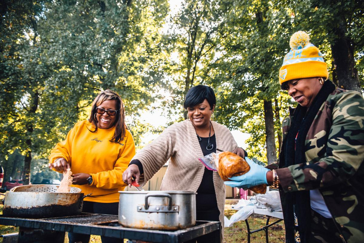 Three Women Cooking Together Outside In The Woods