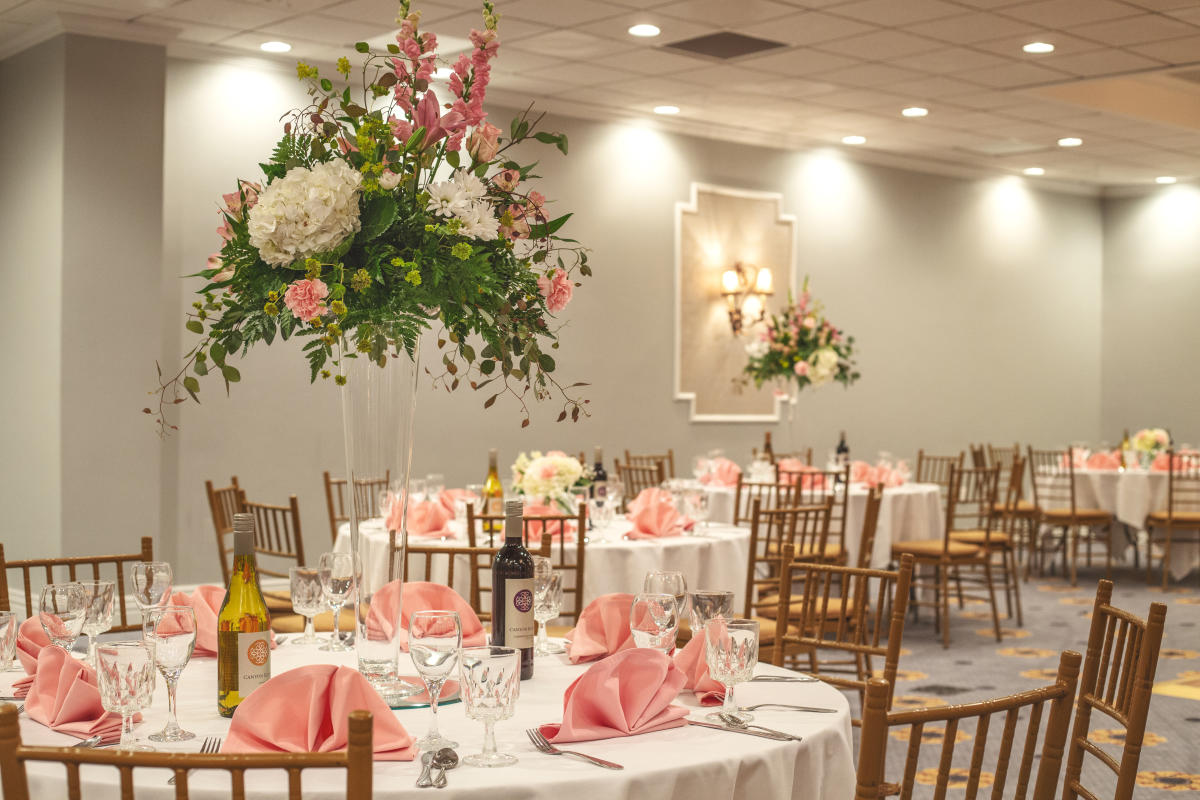 Ballroom set up with pink and white decor and flower center pieces at the MCM Elegante Beaumont