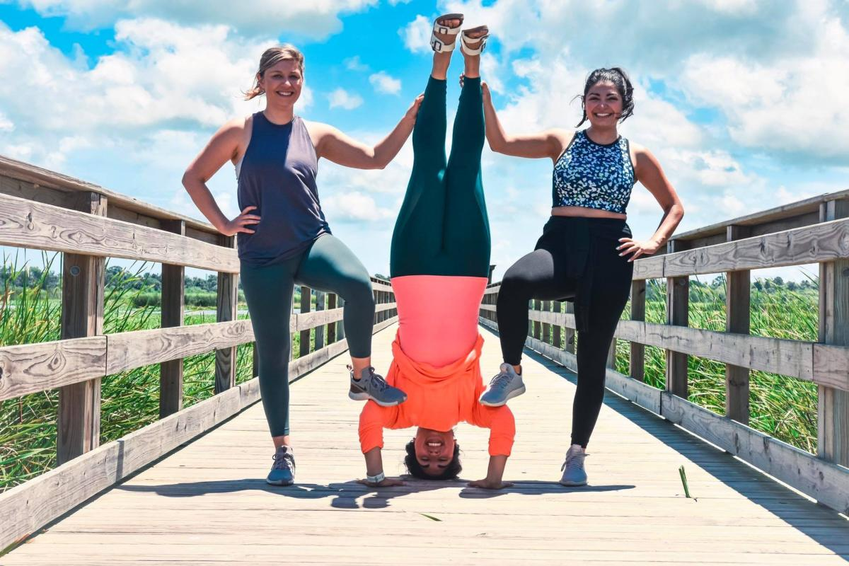 Women in yoga attire posing on the Cattail Marsh Boardwalk
