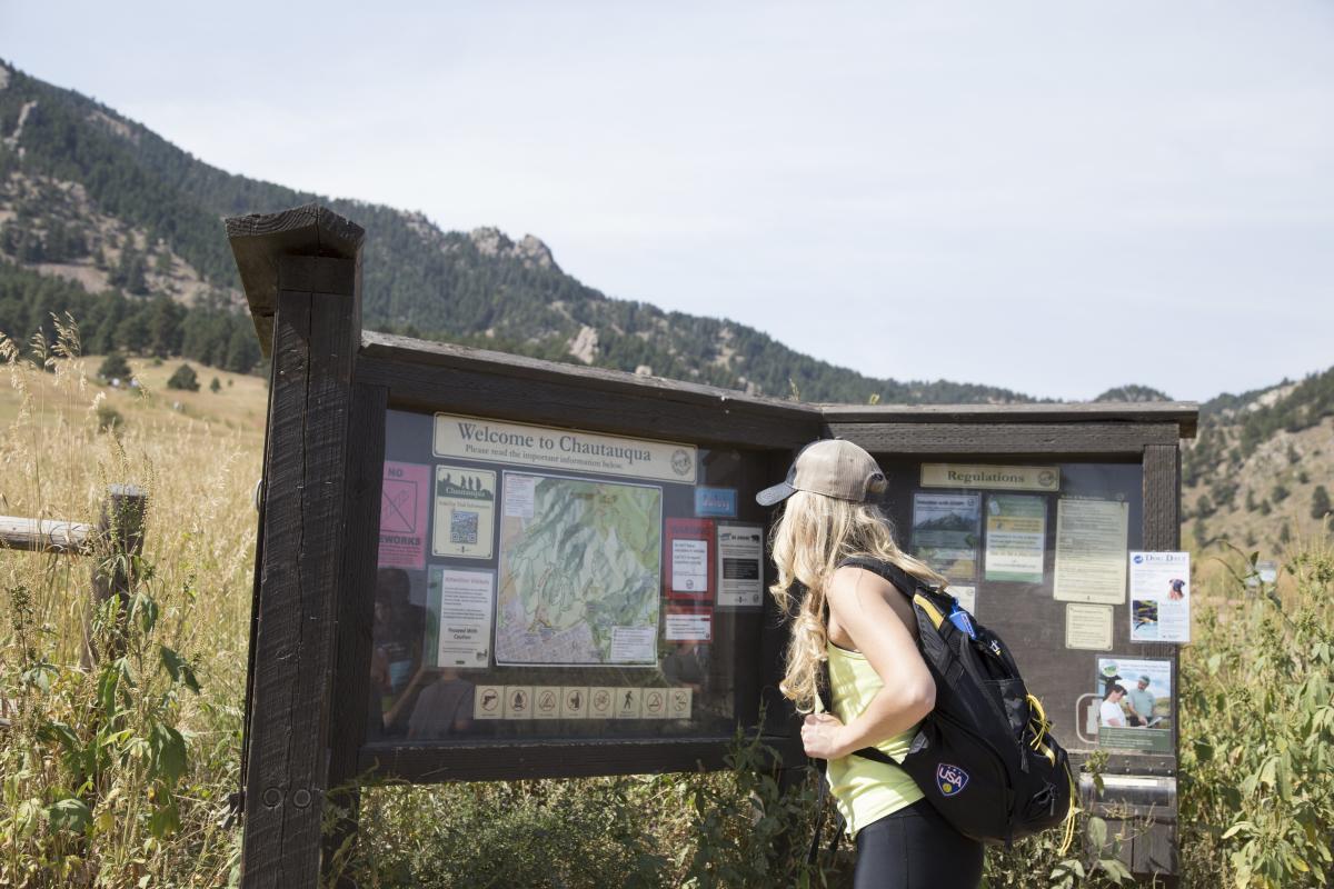 Woman Reading Trailhead Sign at Chautauqua