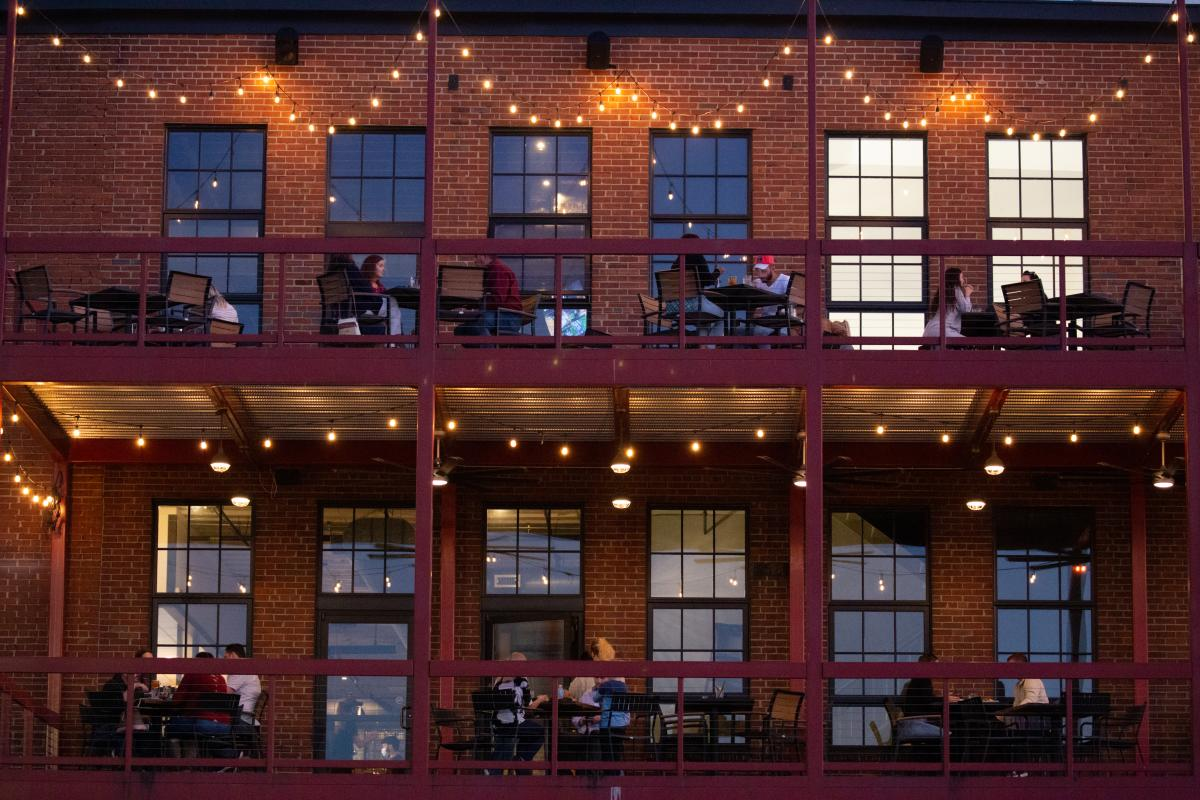people eating outside on a two-story balcony