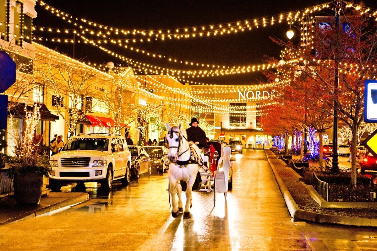 Horse-drawn carriage riding under strung twinkle lights during holiday season at Easton Town Center