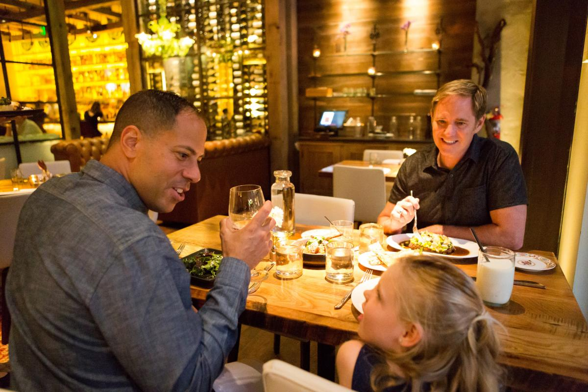 Two dads dining at the Guild House with their daughter