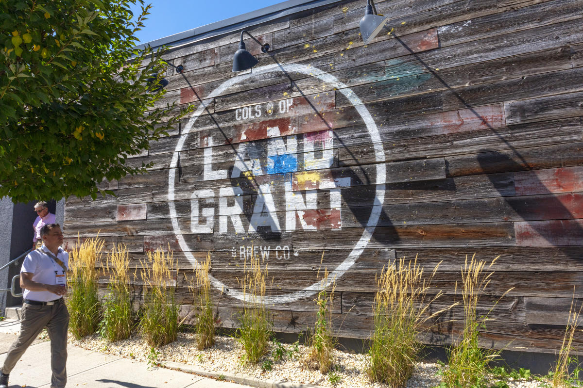 Event attendee walks past the Land-Grant mural outside the brewery facility