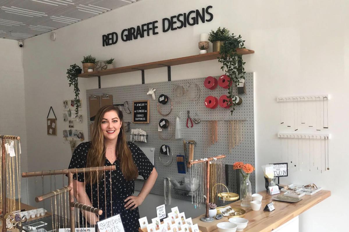 Kate Stevens poses in her shop, Red Giraffe Designs