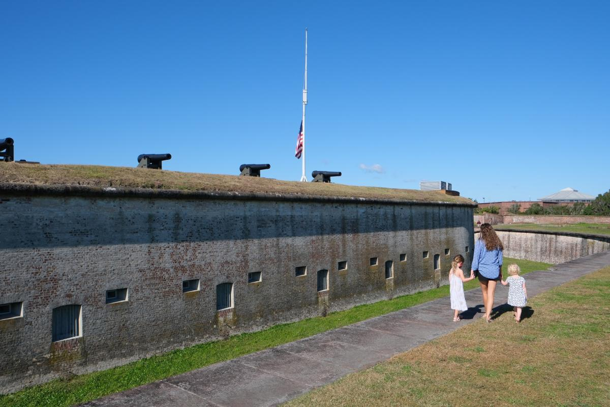 A family strolls along the cannon-lined wall of old Fort Macon State Park.