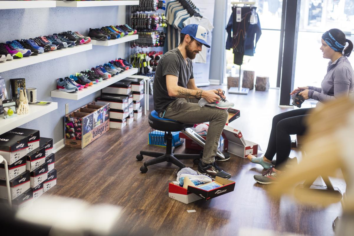 Sales associate helping a women try on shoes at the Blue Ox Running Store