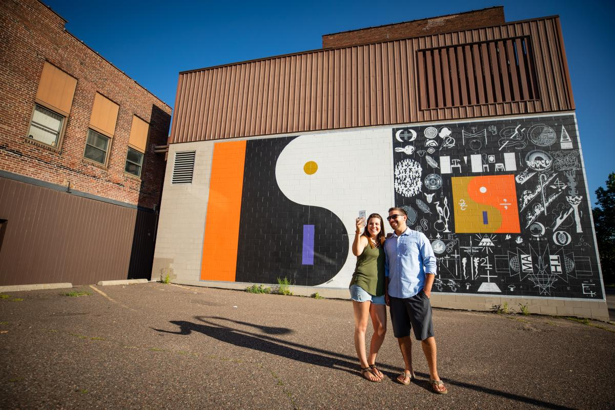 """Couple taking a selfie in front of the """"22 a Million"""" mural in downtown Eau Claire"""