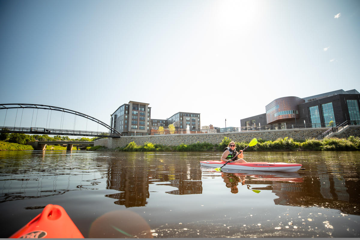 Kayaking at the confluence of the Eau Claire and Chippewa rivers with Haymarket Plaza and Pablo Center in the background