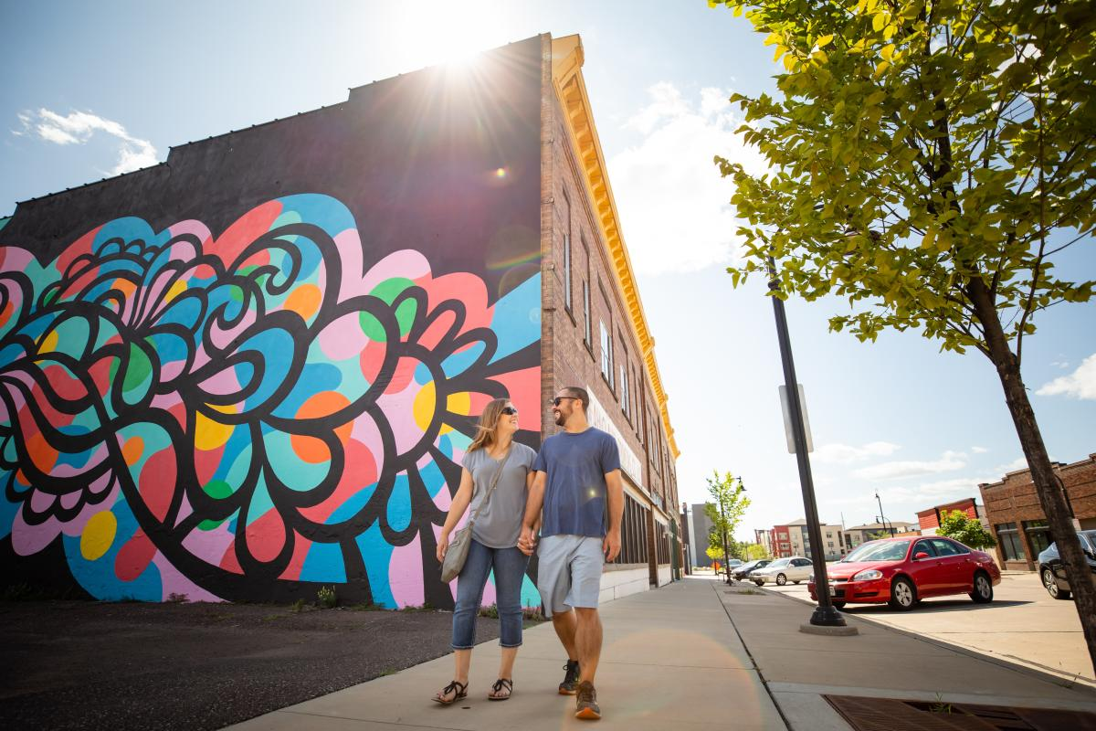 Couple walking past Cascade mural in downtown Eau Claire