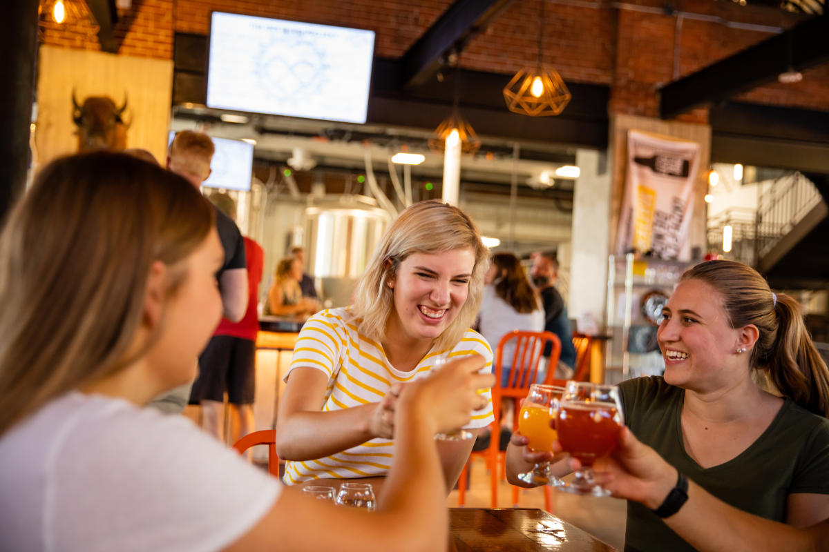 Girls raise their glasses of beers to cheers at The Brewing Projekt