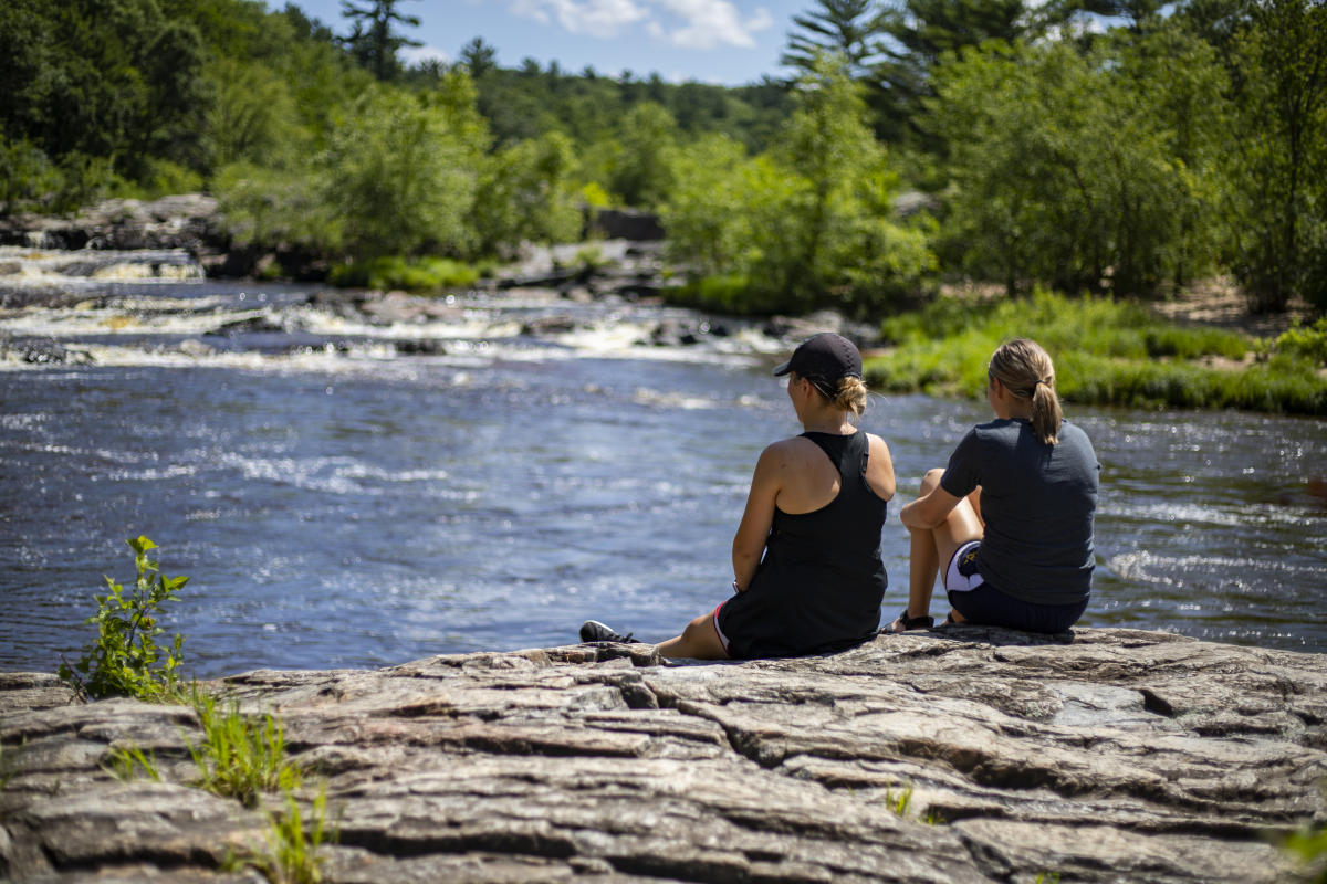 Two women sitting on a rock enjoying the scenic view at Big Falls County Park