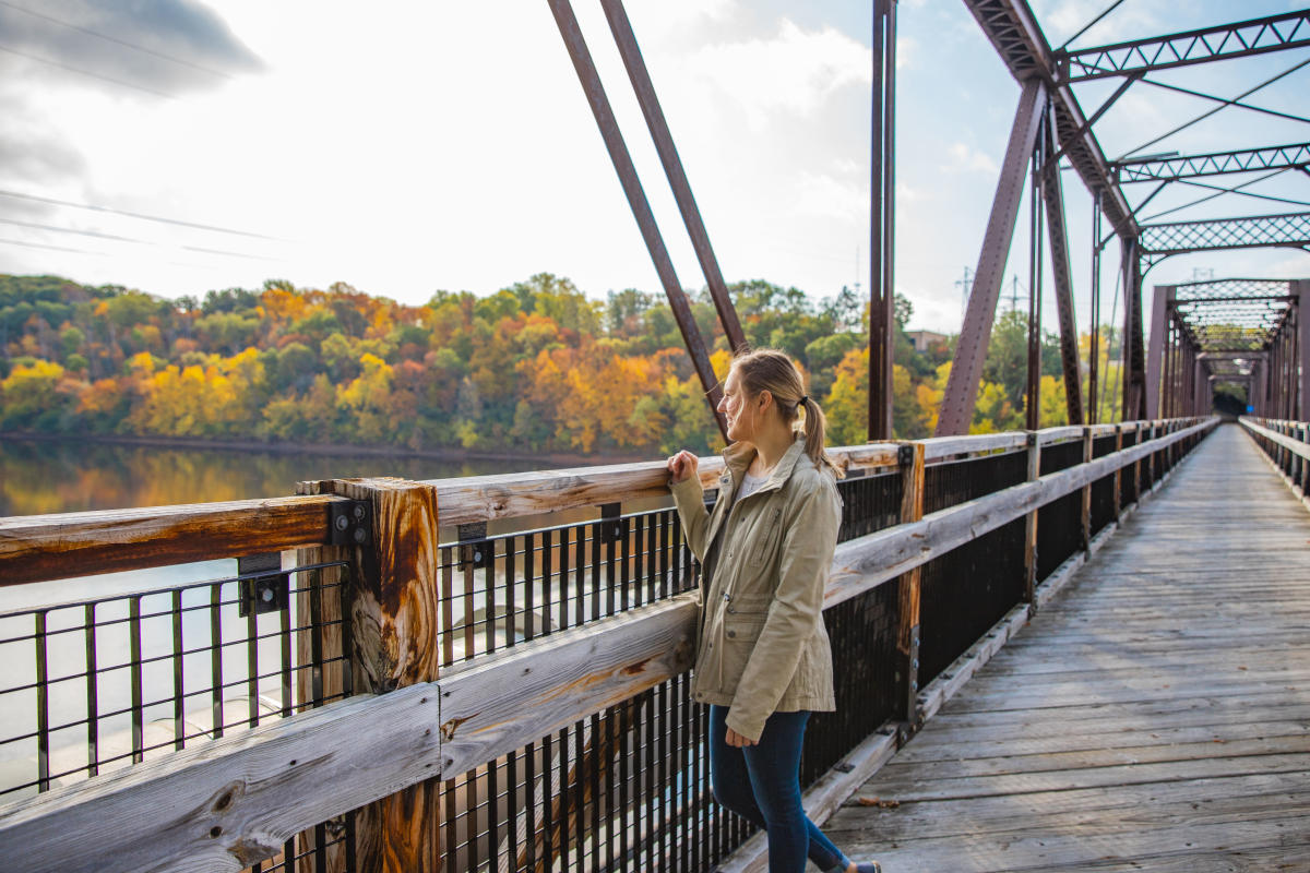 A girl standing on the Clairemont Bridge looking out at the fall colors