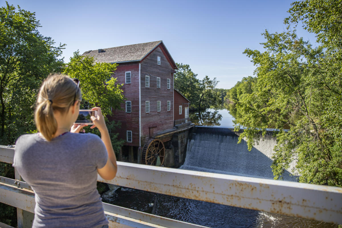 Woman taking a picture of the Dells Mill Museum in the summer