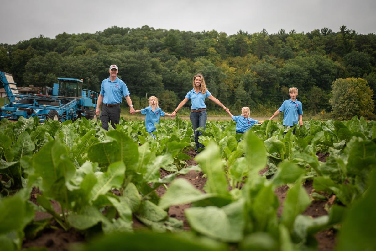 Rygg Family holding hands in a horseradish crop on Huntsinger Farms