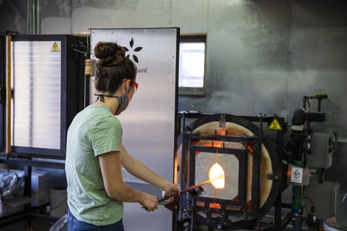 Woman wearing a mask while working In the glass studio at The Glass Orchard