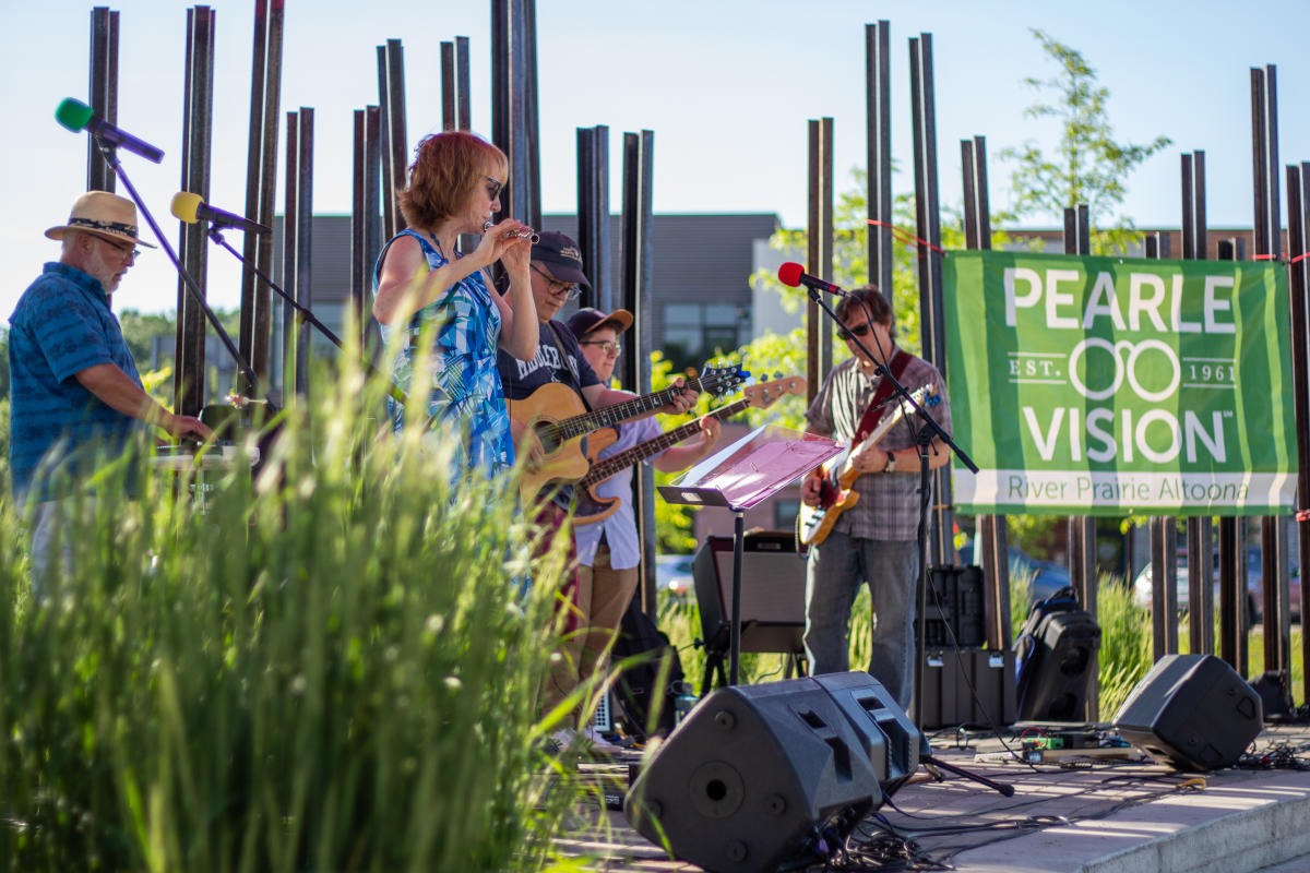 Fusion musicians playing instruments on stage at Four Seasons in River Prairie Park