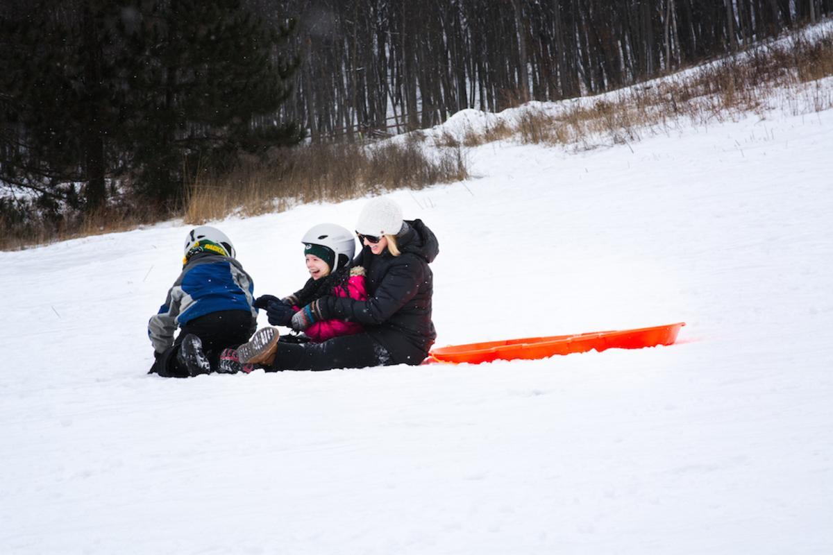 Kids sledding down a hill at Pinehurst Park