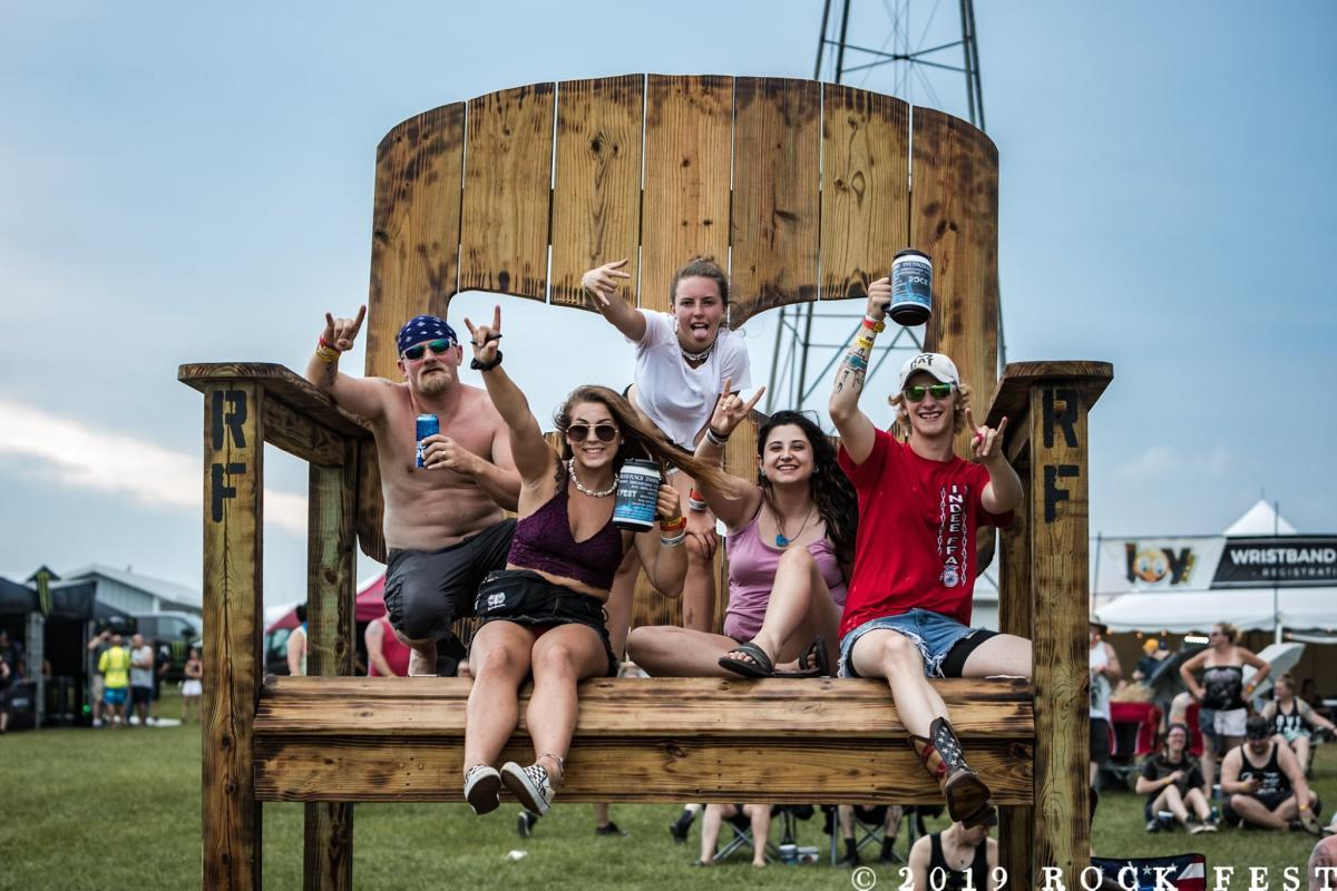 Festival goers sitting on a giant chair at Rock Fest