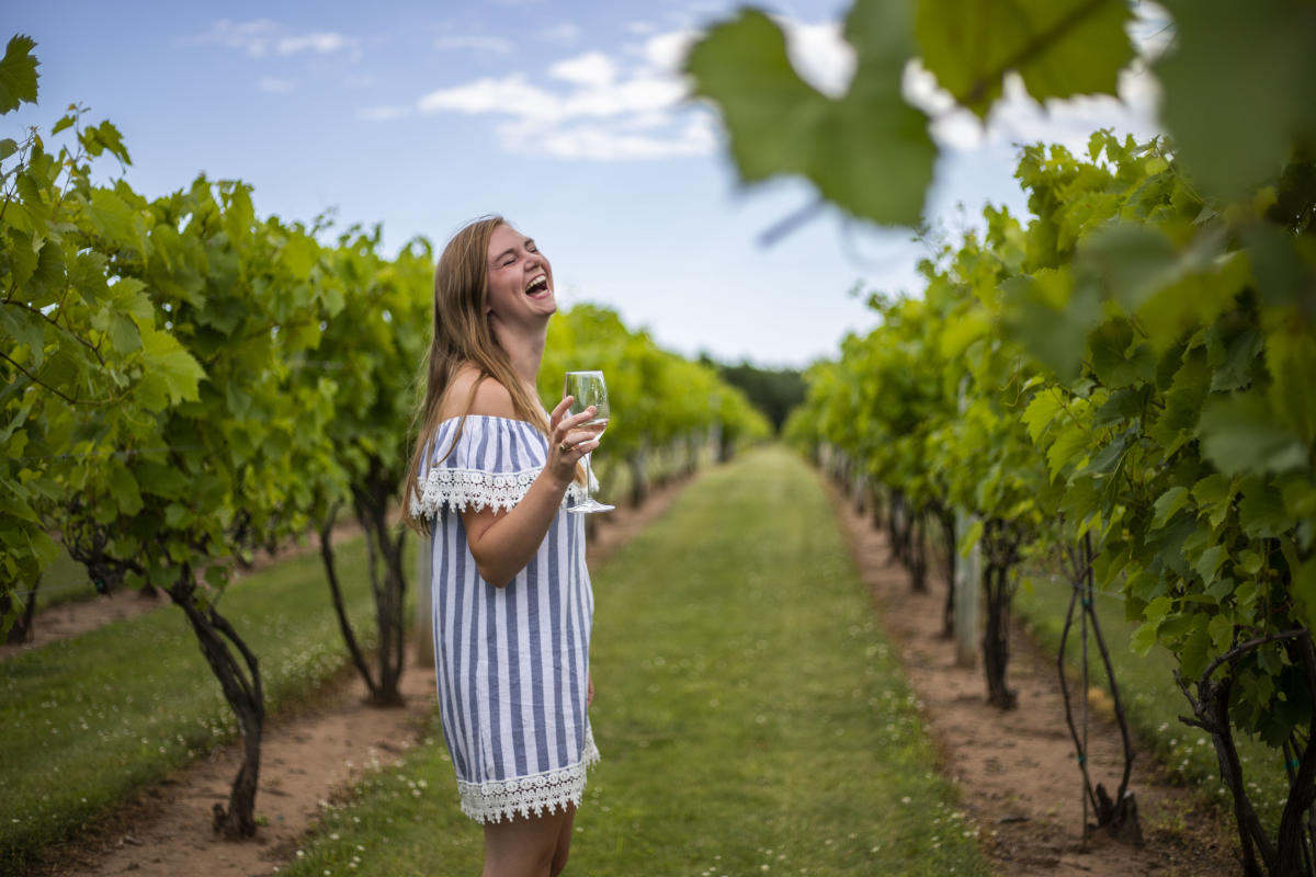 Woman holding a glass of wine, walking down the vineyard at River Bend winery