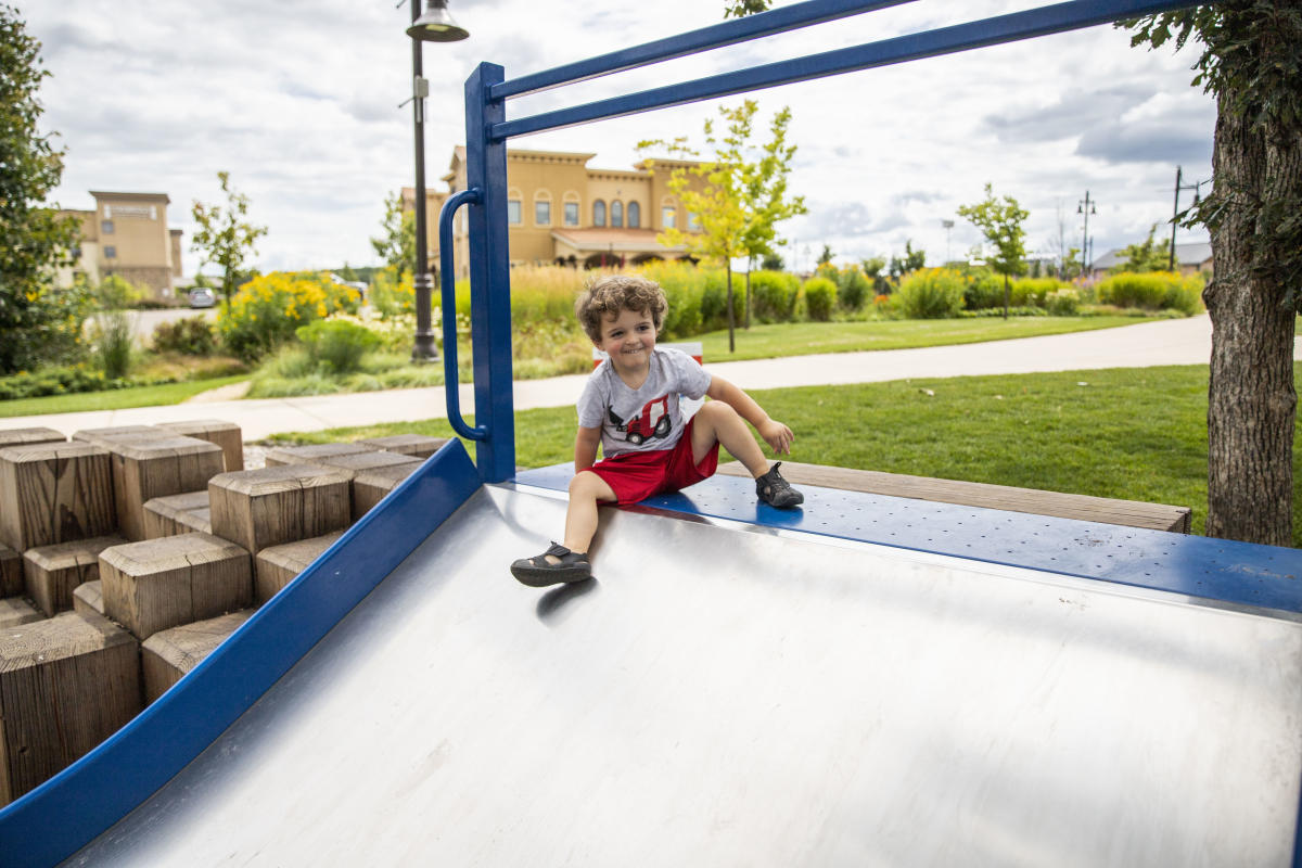 Young boy playing on a slide at the River Prairie playground