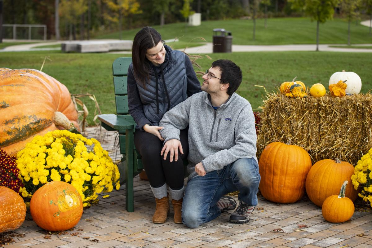 Couple sitting next to pumpkins and hay bales enjoying fall in River Prairie