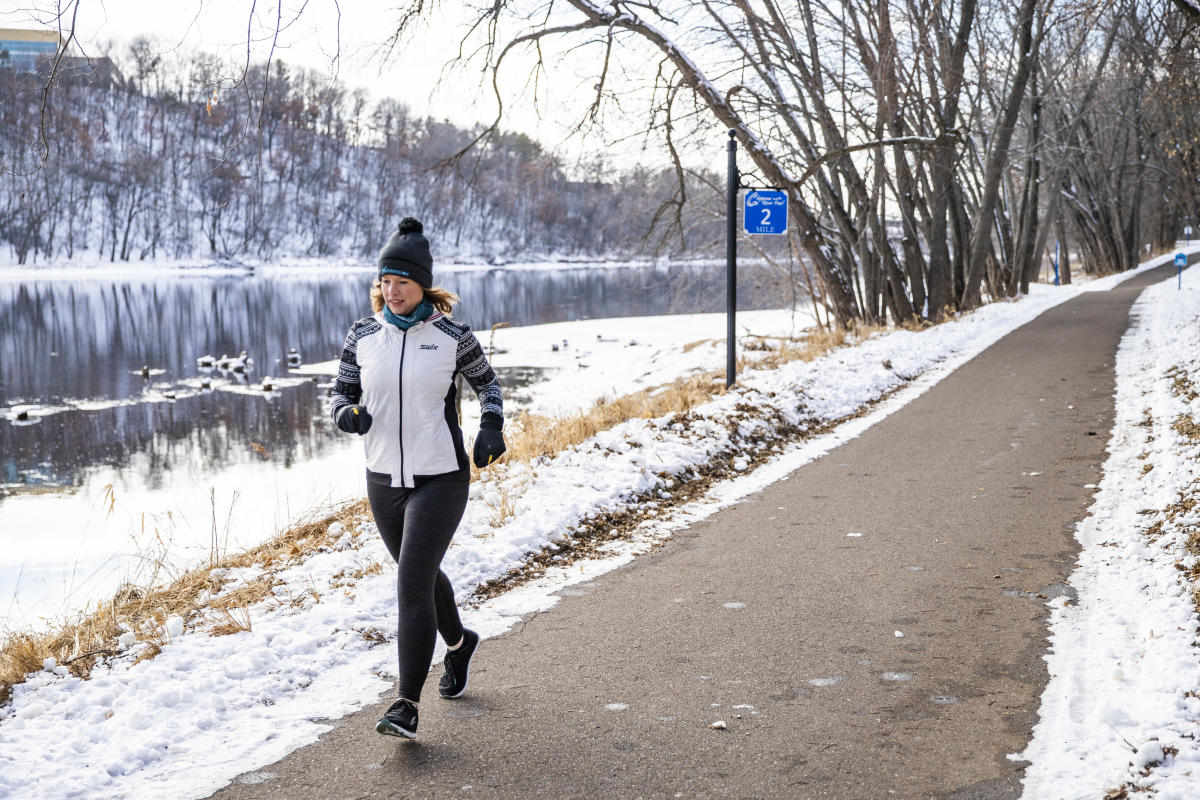 A woman running on the winter recreation path along the Chippewa River in the winter